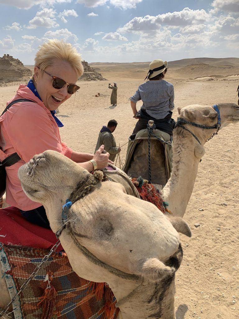 Woman in orange on camel